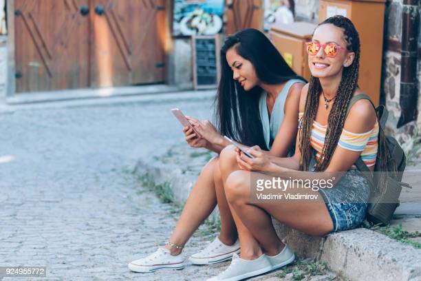 Two girls sitting on street and using smart phones
