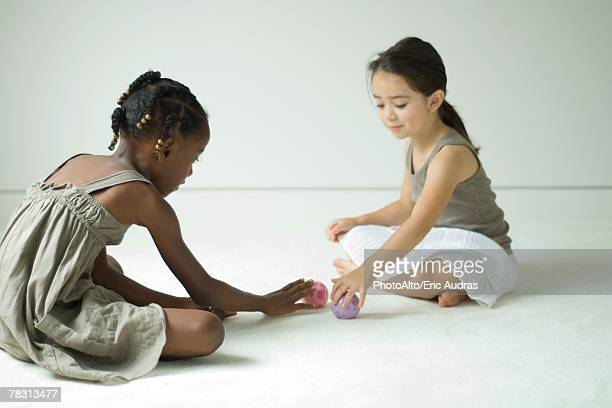 Two girls sitting on the floor playing with toy balls