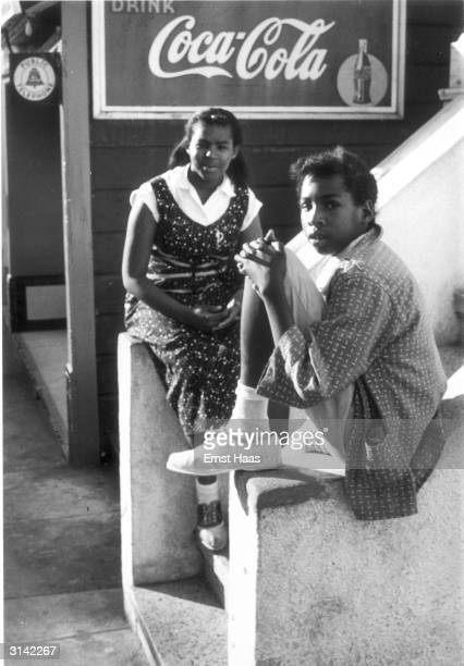 Two girls sitting on the steps of a building in San Francisco California in front of an advertisement for CocaCola