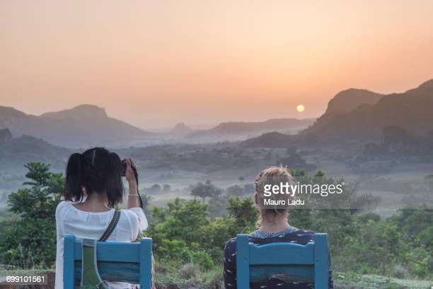 two girls sitting on wooden chairs watching the sunrise above vinales national park from los acuaticos, vinales, cuba - cuba fotografías e imágenes de stock
