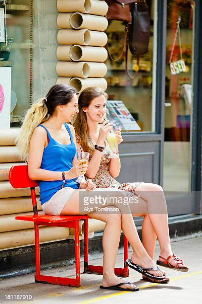 Two girls sitting outdoors drinking juice