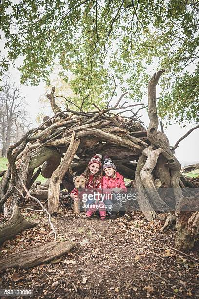 Two girls sitting under log den with dog in Autumn