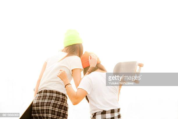 two girls skaters each other snuggle - yusuke nishizawa stock pictures, royalty-free photos & images