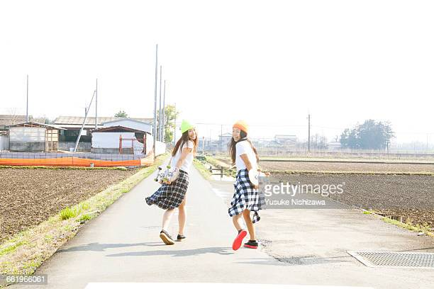 Two girls skaters laugh turned around