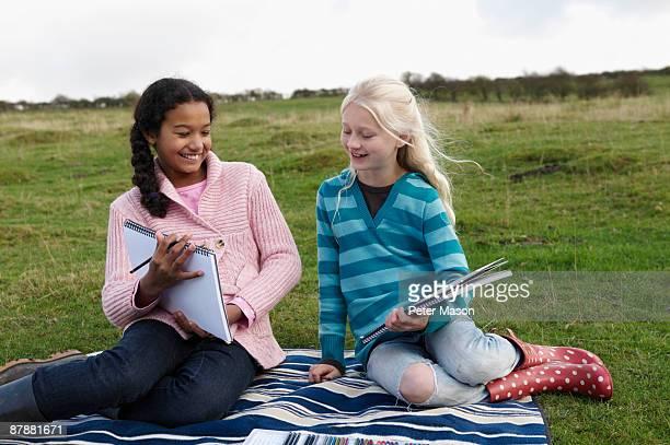 Two girls sketching on hillside