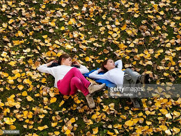 Two girls sleeping on the grass with yellow leaves