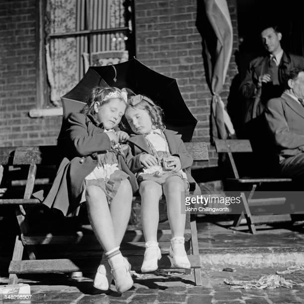 Two girls sleeping under an umbrella at a street party to celebrate the coronation of Queen Elizabeth II held in Morpeth Street in London's East End...