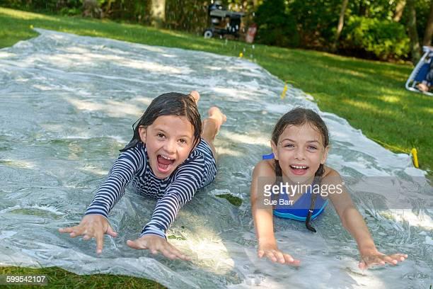 Two girls sliding on slip n slide water mat in garden