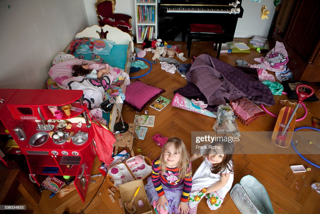 two girls smiling into the camera in chaos room : Stock Photo