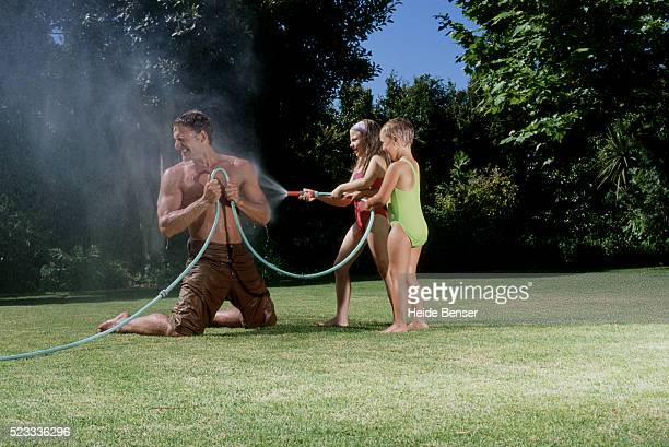 Two girls spraying with hose against their father