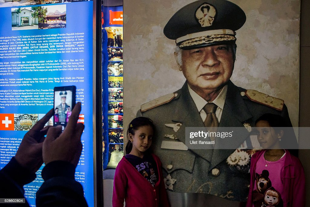 Two girls stand near Soeharto photograph at Soeharto museum on May 06, 2016 in Yogyakarta, Indonesia. Survivors of Indonesia's anti-communist massacres in 1965 called for investigations on the country's purges, in which hundreds of thousands of people are believed to have been killed by the Indonesian military when the Cold War was escalating in Southeast Asia. Based on human rights groups, half a million people died in 1965 during a massacre carried out by the military and religious groups after an attempted coup by suspected communists, where an officer-led group kidnapped and executed six generals on the night of Septemeber 30, 1965. Known as one of the worst mass atrocities of the 20th century, many among the dead had no connection to Communism, and hundreds of thousands had been held in dentention centers for years during the period.