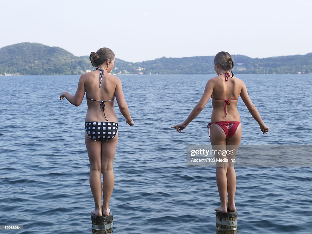 Two girls stand on posts, ready to jump into lake : Stock Photo