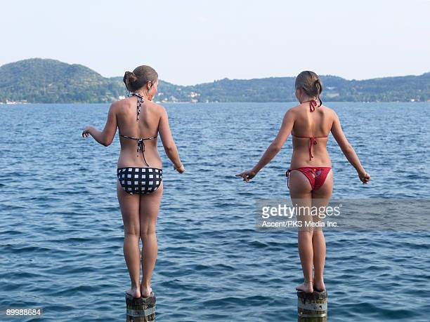 two girls stand on posts, ready to jump into lake - tienermeisjes stockfoto's en -beelden