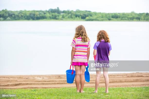 two girls standing at edge of beach in grass - next to stock pictures, royalty-free photos & images