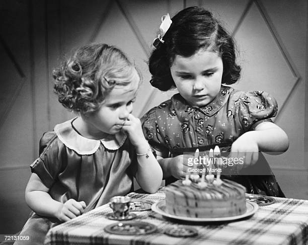 Two girls (4-5) standing at table with birthday cake (B&W)