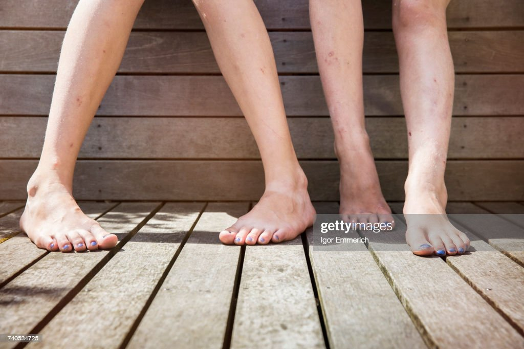 Two girls standing barefoot, view of legs : Stock Photo