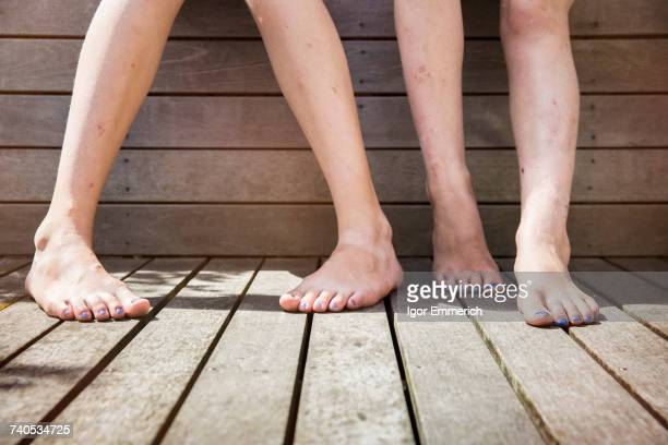 Two girls standing barefoot, view of legs