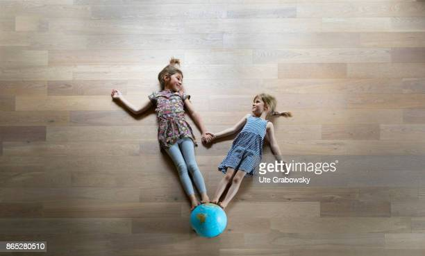 Two girls standing handinhand on a globe and look at each other on August 08 2017 in Sankt Augustin Germany