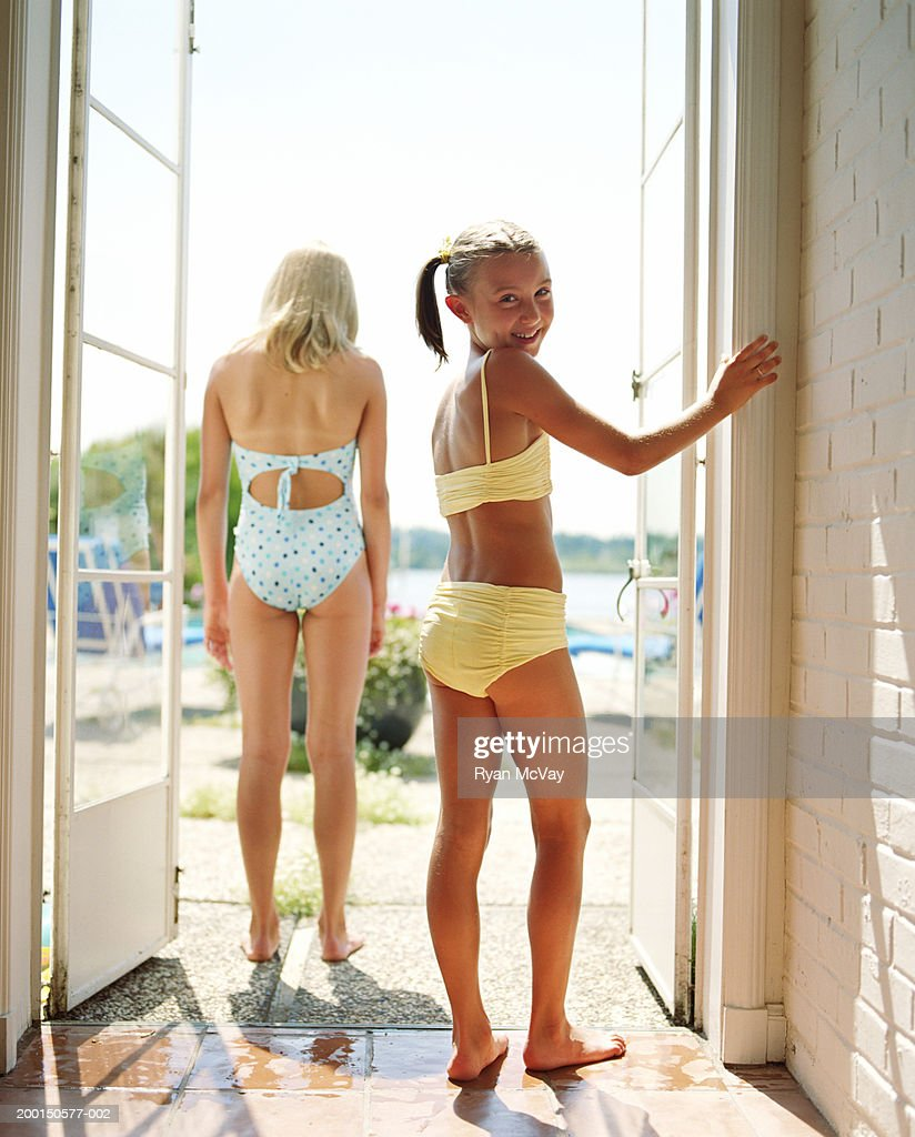 Two girls (9-12) standing in doorway (focus on girl in foreground) : Stock Photo