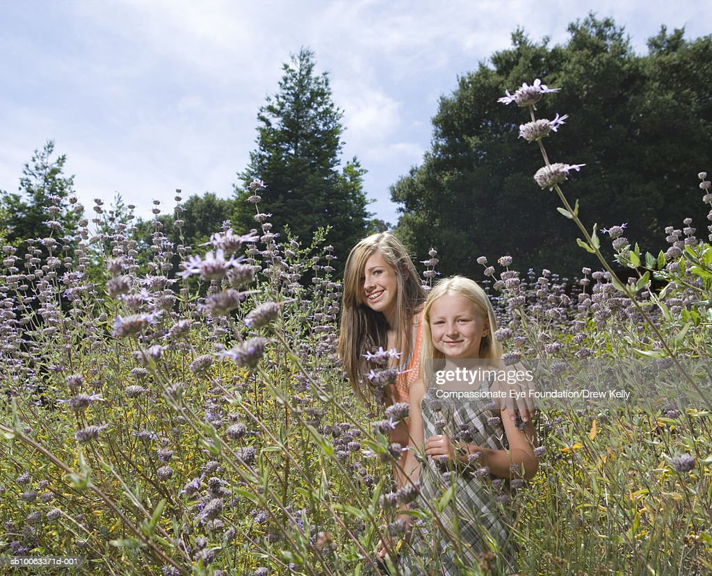 Two girls (8-11 years) standing in field of flowers, portrait : Stock Photo