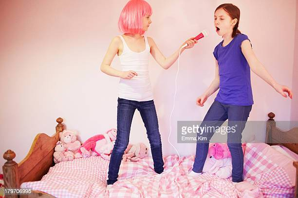 Two girls standing on bed singing into microphone
