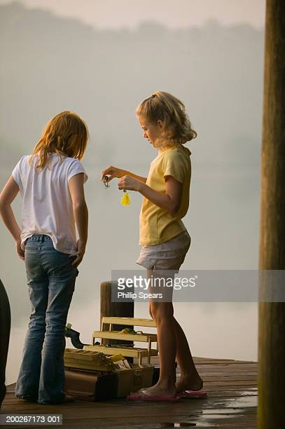 two girls (8-10) standing on dock with fishing gear - girl wear jeans and flip flops stock photos and pictures