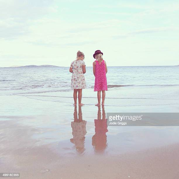 Two girls standing on wet sand at the beach
