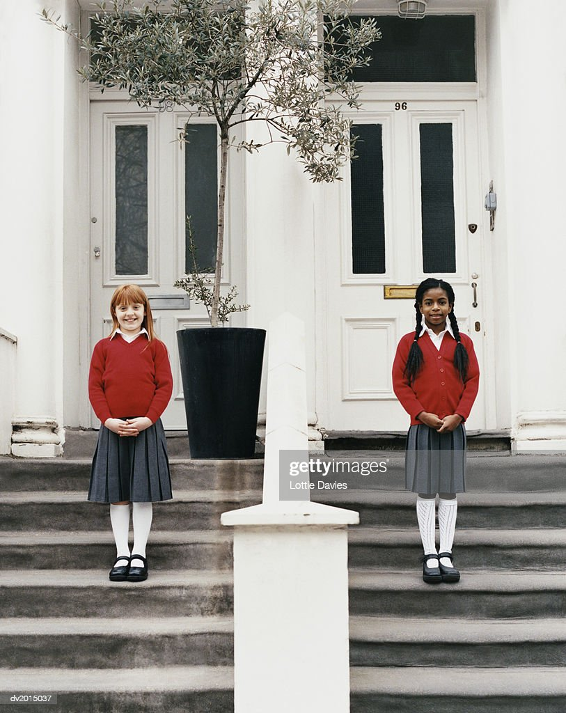 Two Girls Standing Outside the Front Doors of Their Townhouses : Stock Photo