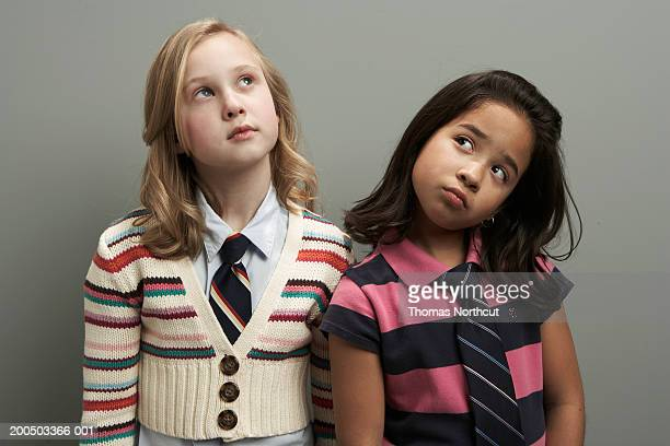 Two girls (8-10) standing side by side, looking up