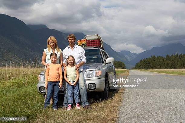 two girls (6-8 years) standing with parents beside car on grass verge, portrait - 30 39 years foto e immagini stock