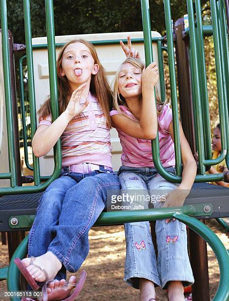 Two girls (8-10) sticking out tongues in playground, portrait