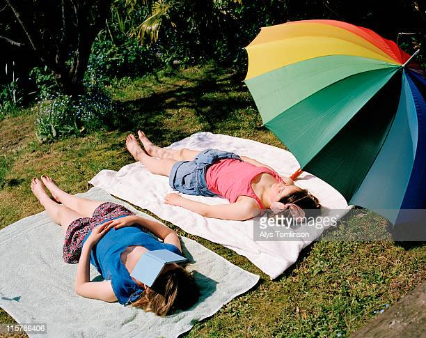 two girls sunbathing in a garden - girls sunbathing stock pictures, royalty-free photos & images