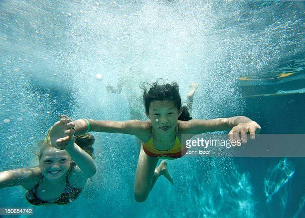 two girls swimming underwater in a pool - chinese bikini girls stock pictures, royalty-free photos & images