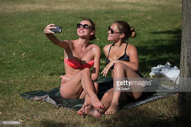 Two girls take a photograph of themselves on their mobile phone as they relax in the warm weather in Hyde Park on July 18 2014 in London England The...