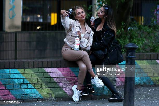 Two girls take a selfie while drinking alcohol on a wall in Manchester's Northern Quarter on April 16, 2021 in Manchester, England. Pubs and...