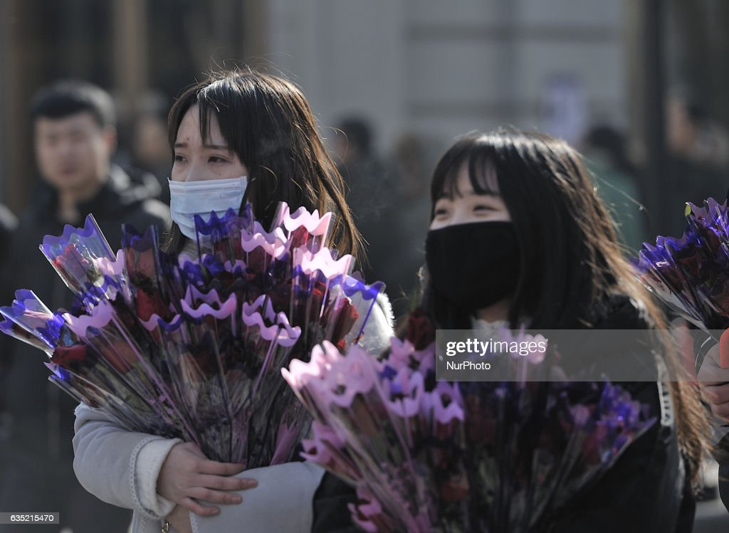 Two girls take flowers on Valentine's Day at central street in Harbin city of China,14 February 2017. Many Chinese couples choose Valentine's Day to celebrate love as the western Valentine's Day becomes more and more popular among young people in China.
