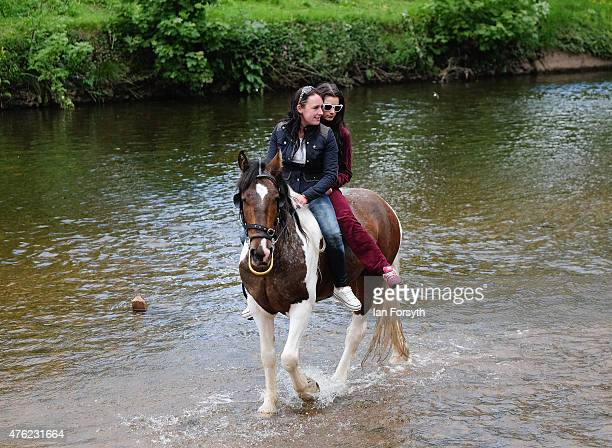 Two girls take their horse into the River Eden during the Appleby Horse Fair on June 7 2015 in Appleby England The fair is an annual gathering for...