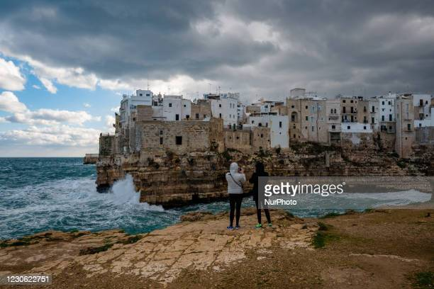 Two girls takes some photos with their smartphone of the storm on Lama Monachile in Polignano a Mare on January 16, 2021. The arrival of the...