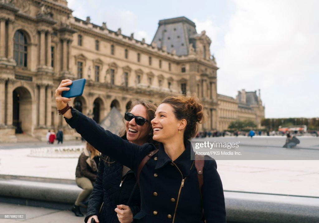 Two girls taking selfie in front of the Louvre : Stock Photo