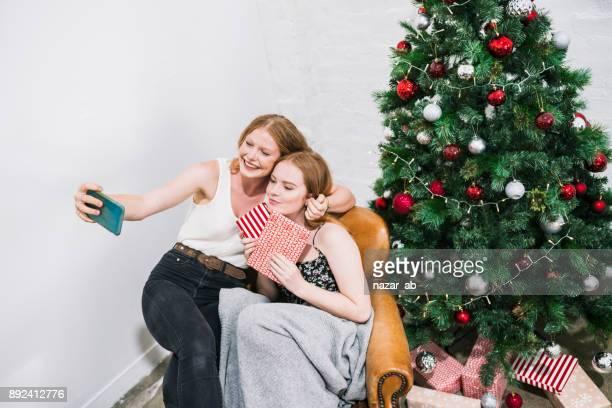 二人の女の子がバック グラウンドでクリスマスの装飾と selfie を撮影します。