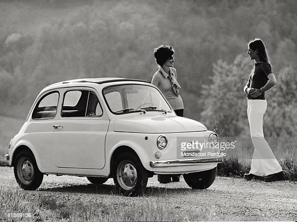 Two girls talking beside a model of Fiat 500 R 1970s
