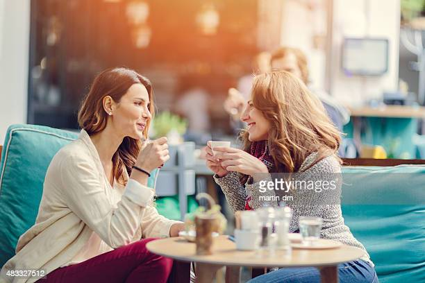 two girls talking in a cafe - pavement cafe stock pictures, royalty-free photos & images
