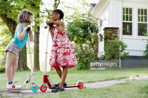 Two girls (7- 8 years) talking in house backyard, leaning on push scooters