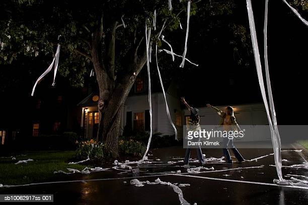 two girls (10-11, 12-13) throwing toilet paper into tree in front of house, night - naughty halloween stock photos and pictures