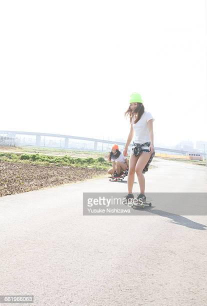 two girls to a skateboard - yusuke nishizawa stock pictures, royalty-free photos & images
