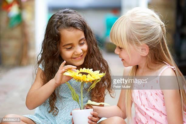 Two girls touching sunflower pot in garden