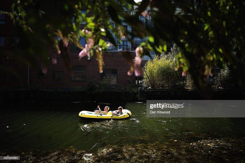 Two girls try and make their way down the Regent's Canal on an inflatable dinghy on July 18, 2014 in London, England. The Met Office has issued a heatwave alert as temperatures soar to their highest of the year.