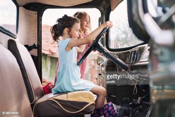 two girls trying to drive an old truck - dirty little girls photos stock pictures, royalty-free photos & images