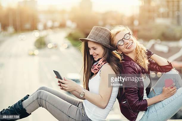 duas amigas usando telefones celulares na cidade - bulevar - fotografias e filmes do acervo