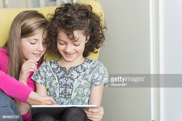 Two girls using digital tablet